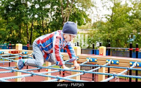 Gracioso niñito clime en el web de la cuerda en el patio de recreo. Chico lindo juego y subir al aire libre en un día soleado de verano