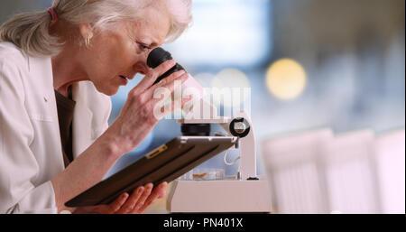 Hembra madura científico toma notas en Tablet PC y utiliza microscopio