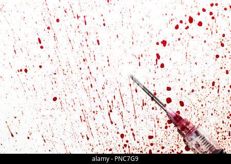 Una jeringa con sangre rociada sobre un fondo blanco.
