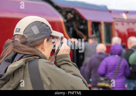 Kidderminster, Reino Unido. El 21 de septiembre, 2018. El día dos de Severn Valley Railway del otoño de vapor ve entusiasmada trainspotters Gala acudiendo a la plataforma en Kidderminster SVR vintage station. A pesar de la lluvia, los entusiastas del tren aprovechar cada oportunidad para llegar lo más cerca posible de estos magníficos UK locomotoras a vapor, particularmente la Duquesa de Sutherland buscando resplandeciente en su fina crimson librea. Una mujer fotógrafo (vista trasera) es visto tomando fotografías de la bulliciosa escena de plataforma en este patrimonio ferroviario. Crédito: Lee Hudson/Alamy Live News Foto de stock