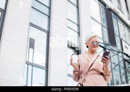 La empresaria a través de teléfono móvil y la celebración de la taza de café contra el fondo urbano Foto de stock
