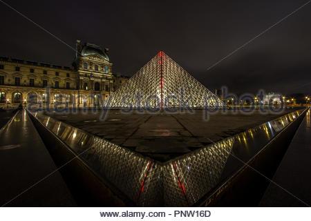 Por la noche el museo del Louvre en París con un rayo rojo sorprendente desde el middtople de la pirámide de vidrio