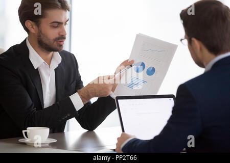 Los gerentes hombres analizando las estadísticas financieras de la empresa en satisfacer