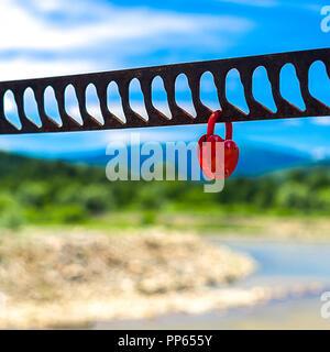 Un solo candado rojo en forma de corazón que simboliza el amor colgando de la barandilla del puente con el río borrosa, vegetación, montañas y cielo azul en segundo plano.