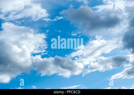 El infinito cielo azul y nubes grises y blancas.