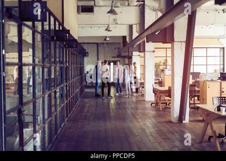 Compartir ideas frescas. Grupo de jóvenes empresarios en smart ropa casual hablando y sonriendo mientras está de pie en el pasillo de la oficina.