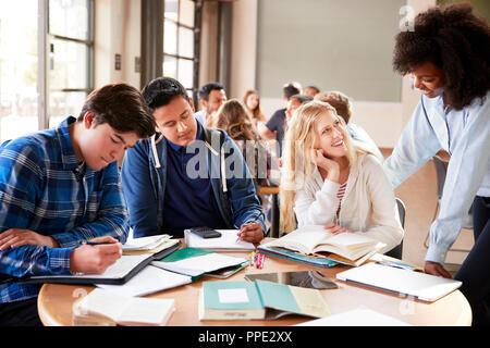 Grupo de Estudiantes de la escuela secundaria con la maestra trabajando en el escritorio