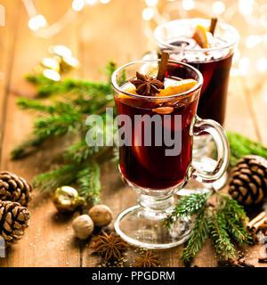 Navidad vino tinto especiado con especias y naranjas en una mesa de estilo rústico de madera. Bebida caliente tradicional en Navidad