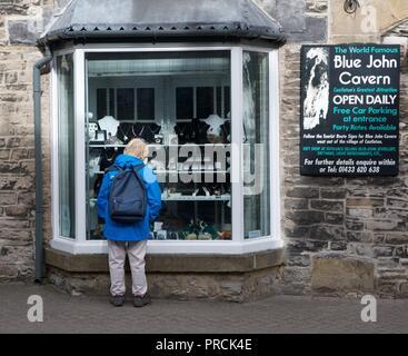 Un visitante mira la mercadería en una tienda windowin Castleton, Derbyshire.