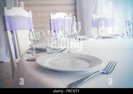 Placa vacía, copas de vino, la horquilla y los cuchillos en la mesa