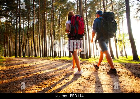 Ruta dura. Hermosa pareja joven senderismo juntos en el bosque mientras disfruta de su viaje.