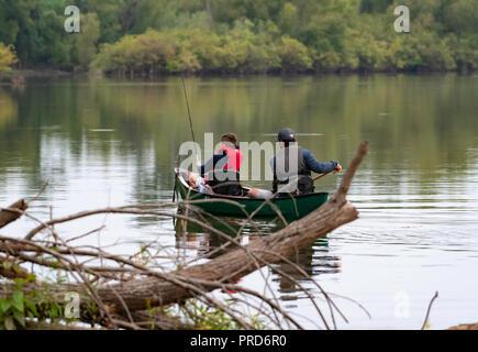 BOSSIER CITY, LA., EE.UU. - 29 de septiembre, 2018: un hombre y el muchacho se ven desde la parte trasera en una canoa en un hermoso y tranquilo lago durante un viaje de pesca.
