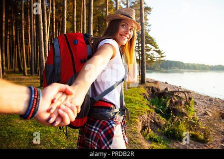 Retrato de mujer joven feliz sosteniendo la mano de su novio mientras caminaba en el bosque.