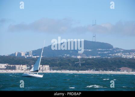 Un velero en el océano Pacífico frente a la costa de San Francisco con Sutro torre visible detrás de él.