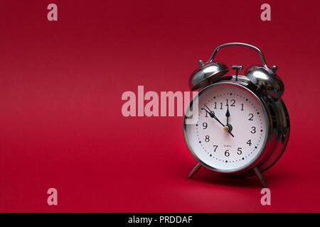 Despertador rojo sobre fondo rojo. close up shot. vista desde arriba. Concepto de tiempo.