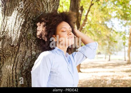 Retrato al aire libre de feliz hermosa mujer afroamericana en la naturaleza, la hembra en camisas azules disfrutar día de verano, apoyándose en el árbol en el parque, los ojos cerrados Foto de stock