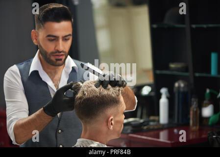 Barber concentrada mirando a cliente y recorte de fresado de joven. Peluquería masculina barbudo y peine recortador sosteniendo en las manos. Guapo master llevando guantes negros.