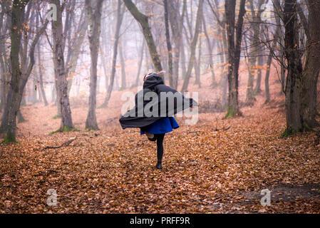 Chica en negro campana huyendo del peligro profundas en la oscuridad del bosque. Una espesa niebla todo alrededor. Aterradora escena de otoño Foto de stock