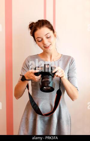 Retrato del fotógrafo chica sonriente y sosteniendo su cámara