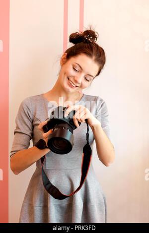 Retrato de mujer joven fotógrafo sonriendo y sosteniendo su cam