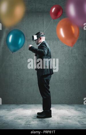 Empresario con VR auricular permanente sobre suelo de cemento y la celebración globo rojo en la mano delante de muchos otros globos de colores