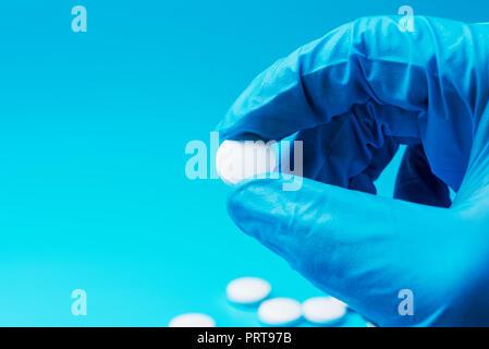 Una mano enguantada posee una pastilla blanca sobre fondo azul. Laboratorio en el centro médico. Foto de stock