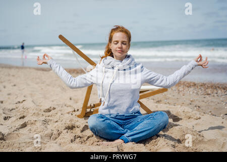 Mujer sentada con las piernas cruzadas sobre la arena, meditando en la playa Foto de stock