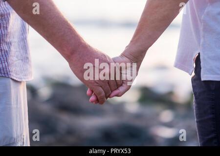 Concepto de vacaciones, turismo, viajes y personas - feliz pareja senior cogidos de la mano. Momento de relajación y serenidad con amor foreverness ethernal