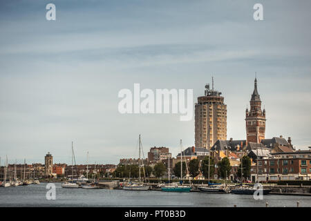 Dunkerque, Francia - 16 de septiembre de 2018: Puerto Viejo con yates a vela y tres torres, LTR: Leughenaer lightower histórico, condominios, Campanario de Dun Foto de stock