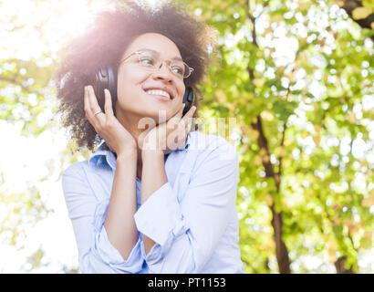 Retrato de hermosa mujer joven Afro Americana feliz de escuchar música con auriculares en la naturaleza, atractivo al aire libre de la diversión hembra de raza mixta
