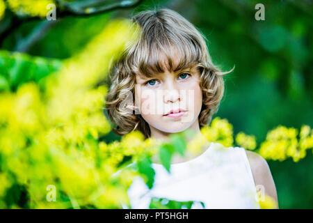 Retrato de joven con flores amarillas en primer plano.