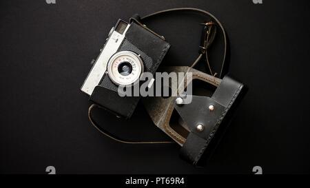 Antigua cámara de película retro en estuche de cuero sobre fondo negro