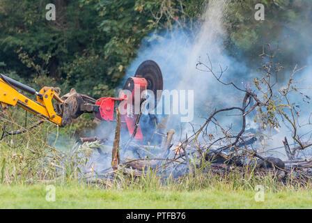 Protech Powerblade PB2000 (2000) doble sierra giratoria montada en un tractor, cortando leña en una hoguera en el campo, en el Reino Unido.