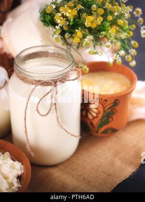 Una lata de leche y otros productos lácteos en la mesa. Todavía la vida en estilo rural. Los productos lácteos de vaca del granjero.