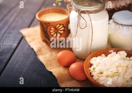 Una lata de leche y otros productos agrícolas en la mesa. Todavía la vida en estilo rural. Los productos lácteos de vaca del granjero.