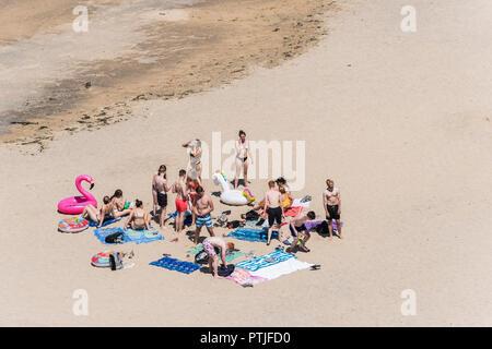 Un numeroso grupo de jóvenes divirtiéndose en una playa de Newquay en Cornualles.
