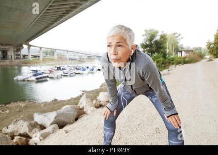 Activa ejecutando Senior Mujer descansando después de correr escuchando música con el smartphone en la orilla del río , entrenar al aire libre.