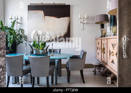 Gran aparador de madera y arte moderno en el comedor con sillas tapizadas