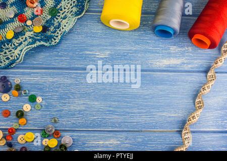 Hilos y botones, cintas de centímetro sobre un fondo de madera azul