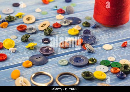 Hilos y botones sobre un fondo de madera azul