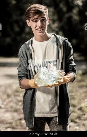 Morena alumno decepcionados después de limpiar el bosque de muchas botellas