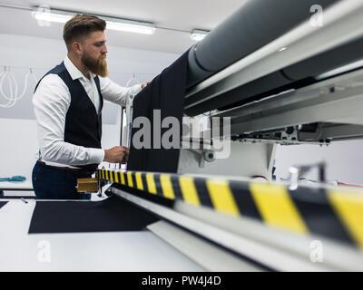 Joven barbudo sastre trabajando en un nuevo diseño de ropa
