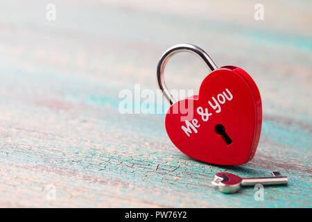 Candado en forma de corazón con una tecla azul de fondo de madera. Espacio de copia