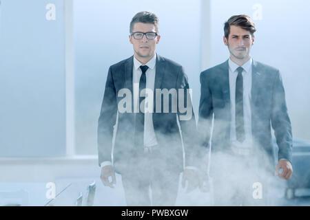 Jóvenes empresarios en una oficina ahumado