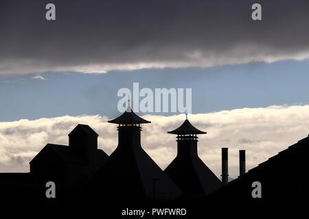 Los dos hornos en el Highland Park Distillery en Orkney, Escocia, con sus tapas en forma de pagoda distintivas siluetas contra el cielo azul, las nubes.