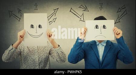 Empresario y empresaria que cubrían sus rostros con hojas con dibujados emoticonos alegre y triste, como una máscara para ocultar su verdadera emoción a partir de la sociedad. Foto de stock