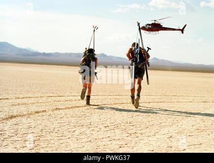 Pareja joven aventurero llevar equipamiento deportivo sobre su espalda debajo de helicóptero estacionario mientras se ejecuta a través de un desierto.