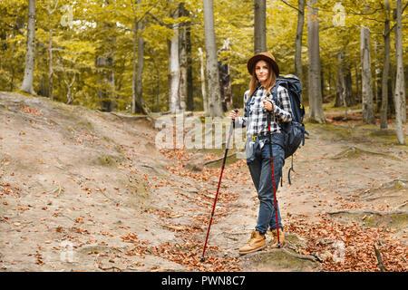 Sonriente joven mujer vistiendo hat trekking en las montañas y tener un descanso relajante, ella se está hospedando y manteniendo el senderismo polacos, viajando concepto
