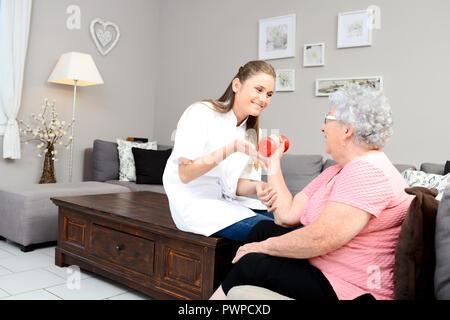 Joven enfermera fisioterapeuta ayudando a las mujeres de edad la rehabilitación física en casa