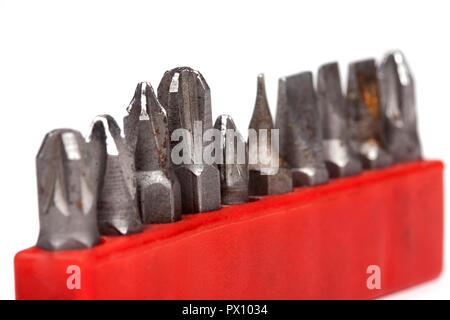 Colección de antiguos rusty portabrocas de un taladro en un caso aislado rojo sobre fondo blanco, macro closeup